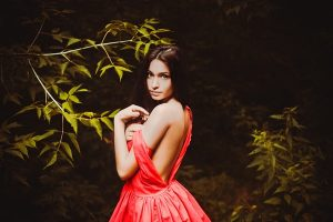 Beautiful woman in orange dress showing her flawless back skin and shoulders