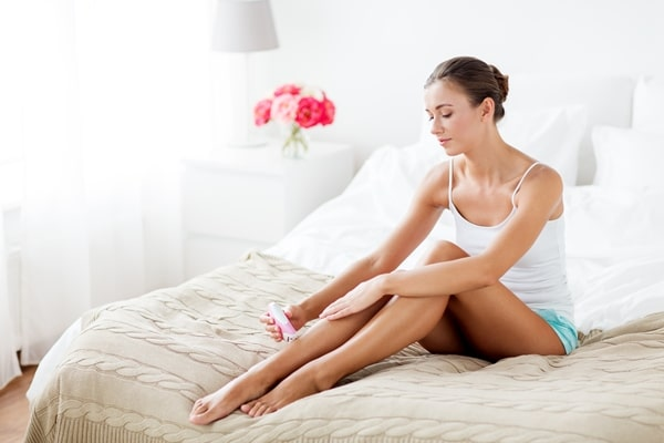 Woman sitting on a bed while applying argan oil product to her legs