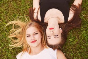 Brunette and blond girls lying on the green grass
