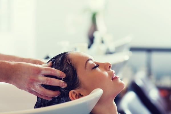 Woman getting her hair shampooed by an assistant