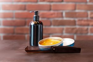 Bottle of castor oil, oil blend, and a comb on a wooden table over a brick wall