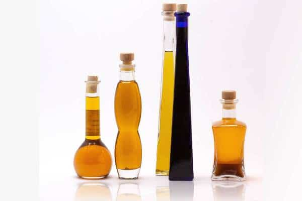 Bottles of different castor oil types in white background