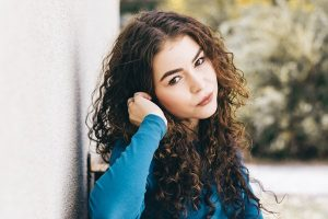 Beautiful girl with curly hair in cobalt blue sweatshirt