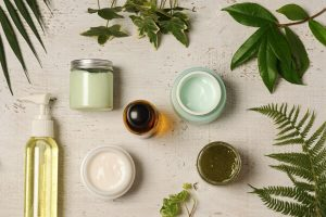Overhead shot of cosmetic products on a white surface, embellished with a few green leaves