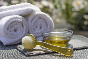 Towels, a dry brush, and a bowl of argan oil as carrier oil for massage