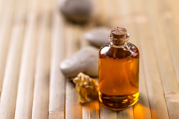Bottle of jojoba oil on bamboo surface