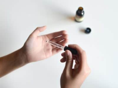 Hands of a product tester putting drops of essential oil on palm for review
