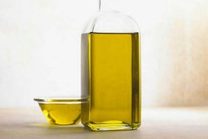 Castor oil in clear glass bottle and small glass bowl